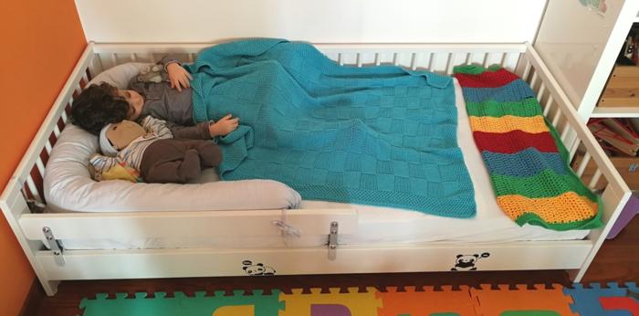 lit bébé sans barreau, meuble bas en bois blanc, tapis en couleurs vives effet puzzle, chambre montessori, enfant qui dort avec une grande poupée, couvert de sa couverture en bleu pastel