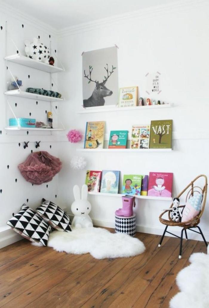 cabane lit, chambre montessori, étagères blanches, panneau décoratif avec un cerf gris fumée, sol recouvert de parquet marron foncé, coussins en noir et blanc avec des motifs graphiques