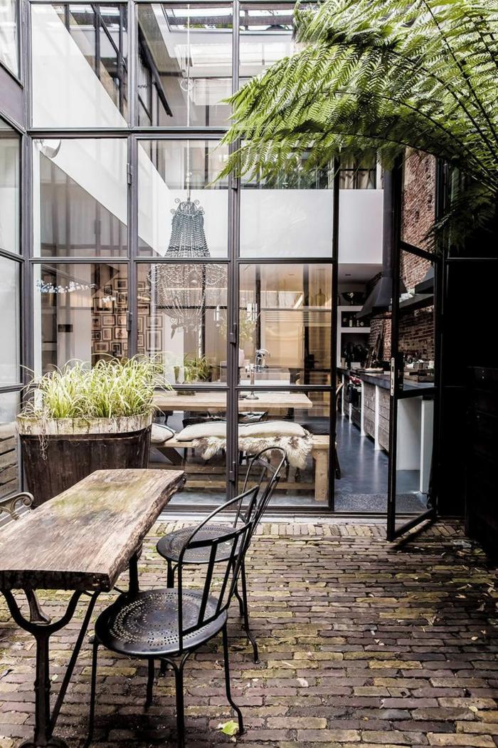 cuisine industrielle avec grande verrière du plafond au sol, table en bois design indus, deux chaises noires vintage, cuisine impressionnante