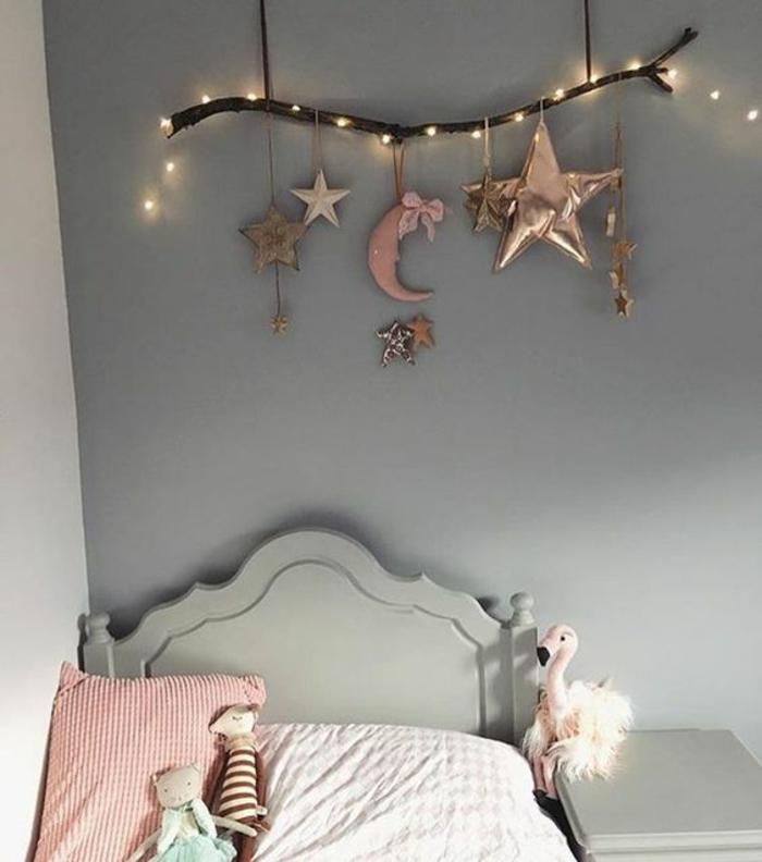 guirlande ampoule enroulée autour d'une grande branche d'arbre naturel et suspendue au-dessus du lit, chambre d'ado aux murs en gris pastel