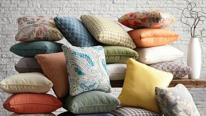 meuble relooké avec une multitude de coussins, mur en briques blanches, vase blanc avec des bambous, customiser un meuble