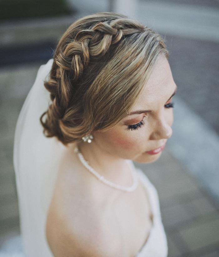 chignon tressé mariage avec une tresse autour de la tete couronne et meche de coté, collier d eperles blanches