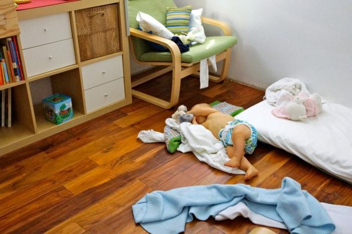 meuble de rangement avec des casiers blancs aux poignées rondes, miroir montessori, fauteuil en tissu vert réséda et bois PVC blanc