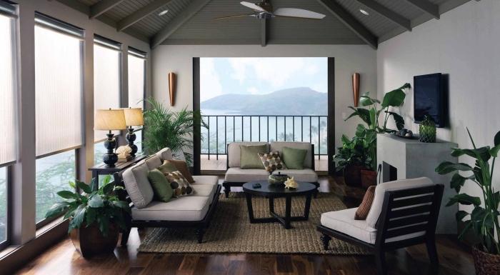 design intérieur dans un salon exotique au plafond en poutres bois peint en vert et meubles de bois foncé