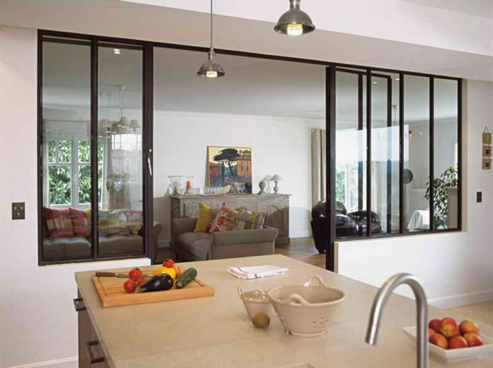 cuisin et salon séparés avec une verrière d'atelier, ilot de cuisine central, sofa gris avec plusieurs coussins déco