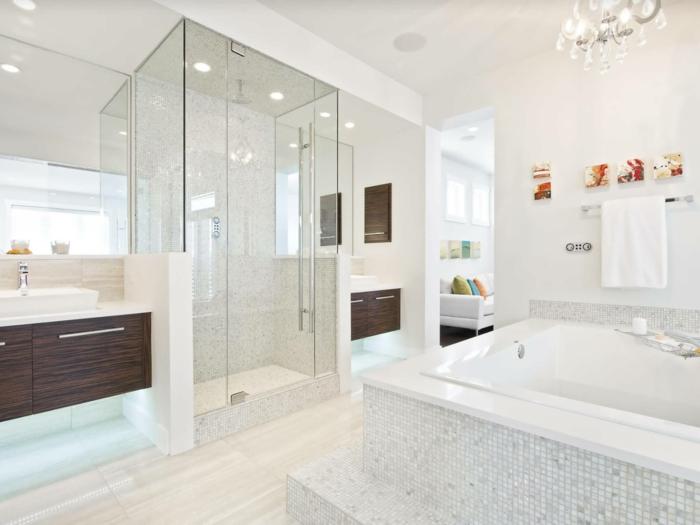 porte coulissante verriere, douche italienne, baignoire blanche avec carrelage gris et blanc, lustre pampilles en cristal, parquet blanc et beige