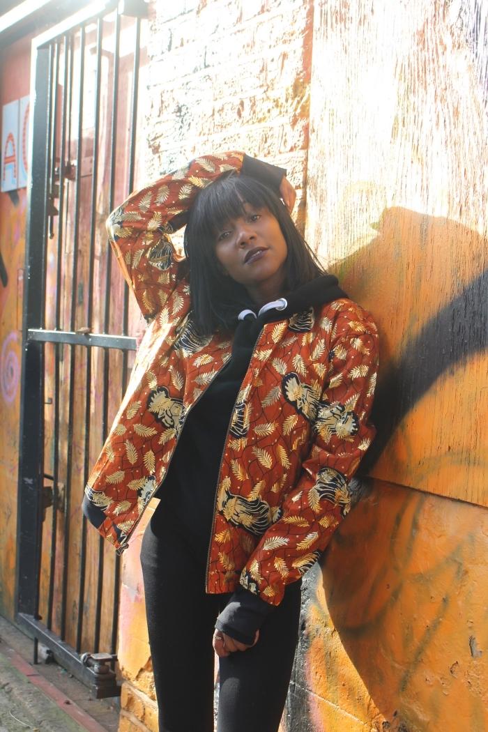 total look noir réveillé par un bomber original en tissu wax à motifs floraux sur fond orange