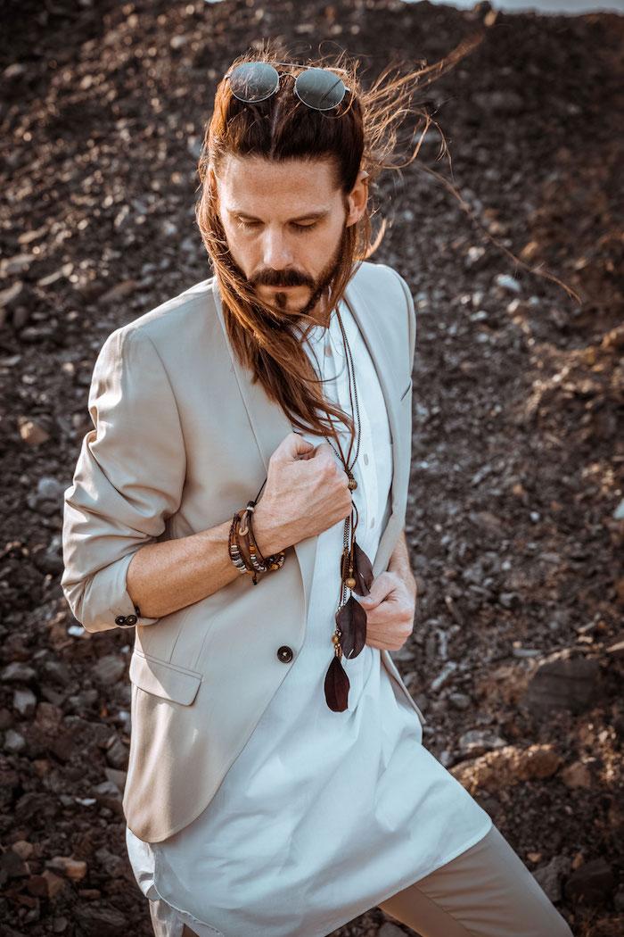 idée de tenue bohème chic homme avec costume beige et chemise sherwani blanch pour homme à cheveux longs