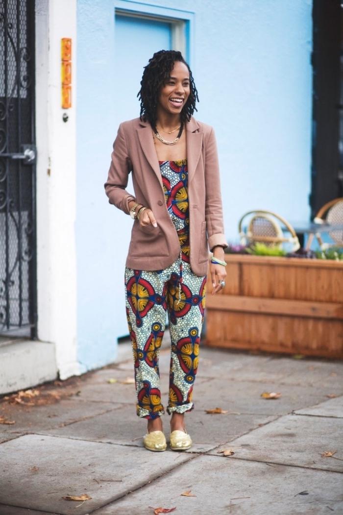 une combinaison pantalon légère à motifs africains assortie à un blazer rose poudré pour donner un côté chic à la tenue