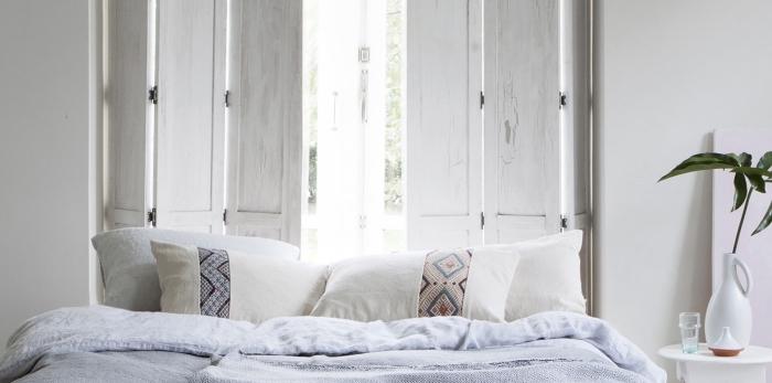 decoration boheme dans une pièce blanche avec grande fenêtre et lit couvert de coussins blancs à motifs ethniques