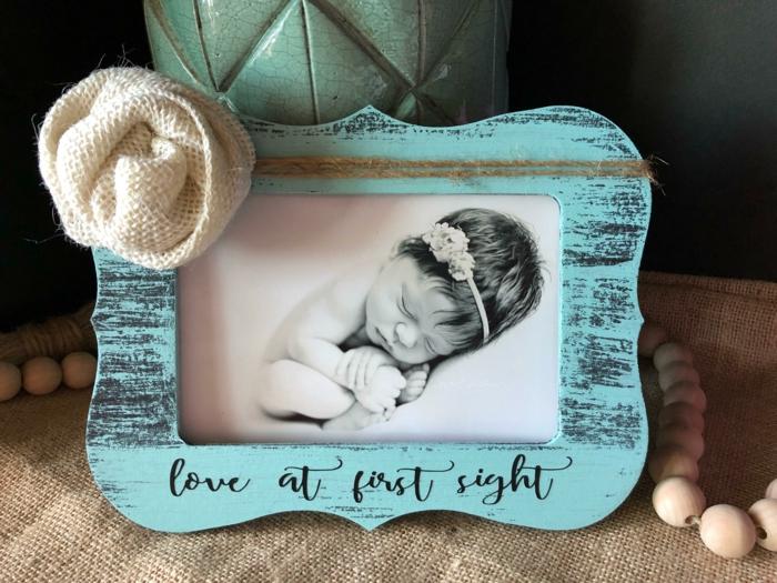 cadeau future maman, cadre photo en bois turquoise, rose en tissu blanc lin sur le cote gauche en haut, photo de bébé qui dort