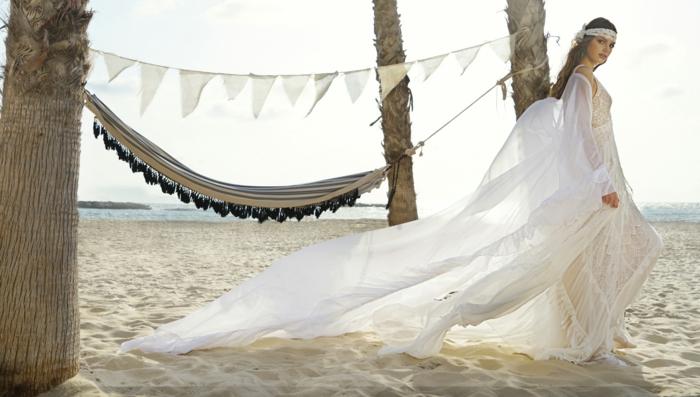 robe hippie chic en dentelle, robe de mariée bohème, cheveux longs avec bande en dentelle blanche sur la tete, hammock étendu entre des palmes