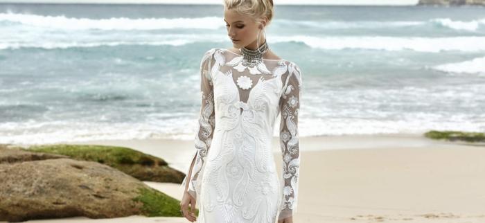 robe blanche boheme, manches longues moulantes, femme mariée qui marche sur une plage, robe moulante