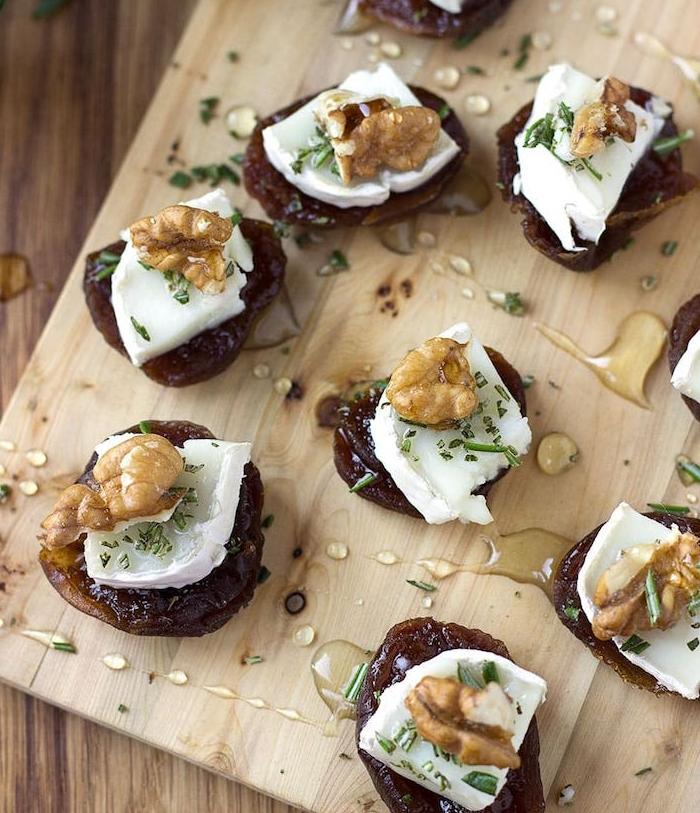 abricots séchés avec du fromage de chèvre, noix et du miel servis sur une planche à découper avec des herbes fraiches