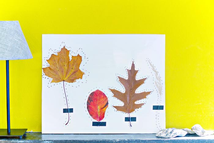 creation deco land art avec des feuilles mortes collées sur un bout de papier blanc et des contours