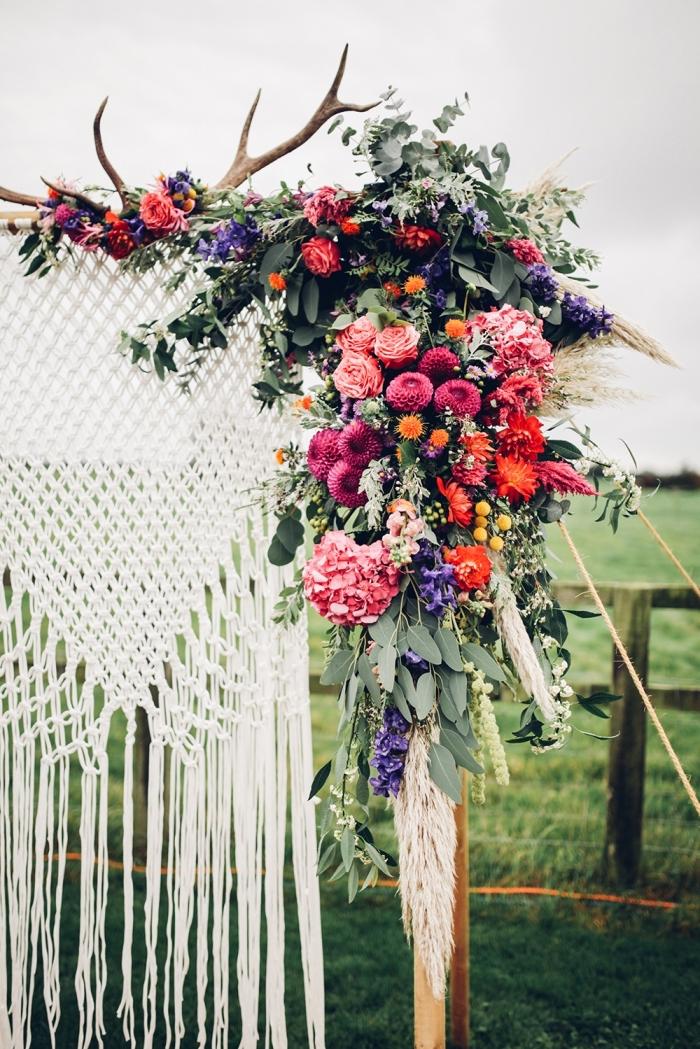 idée décor de mariage en style bohème avec un arc en bois fleurs et rideaux en technique macramé, déco diy de mariage avec noeuds macramé
