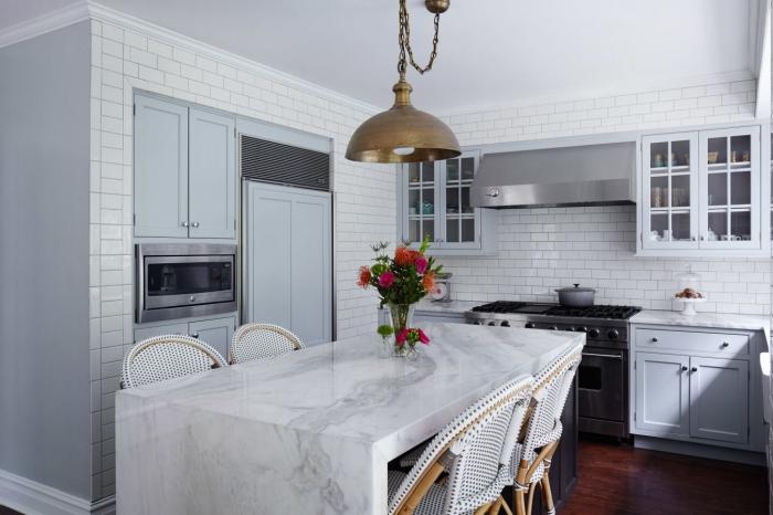 plan de travail ilot central conçu entièrement en marbre blanc qui offre un point convivial dans cette cuisine en gris et carreaux de métro
