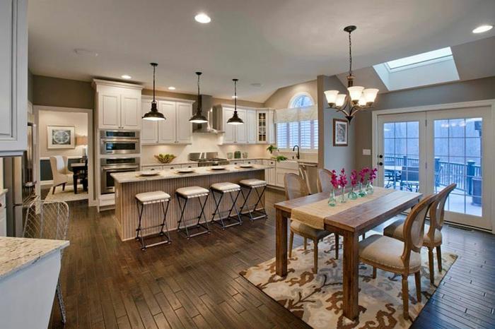 cuisine semi ouverte élégante, sol en bois, table de repas en bois, lampes pendantes noires