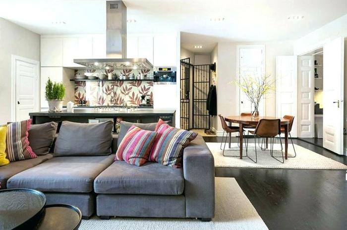grand soda gris, tapis blanc, aménagement cuisine ouverte, coussins déco rayés, table de repas ronde
