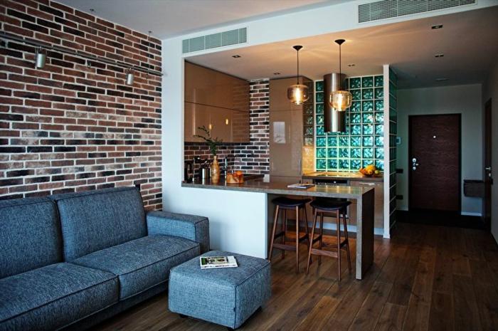 sofa bleu, mur briques, petite cuisine avec bar gris et cloison partielle, lampes pendnantes