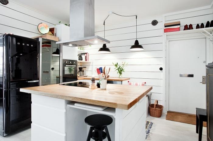 cuisine blanche et bois aménagée dans un style vintage scandinave aux accents noirs équipée d'un ilot de cuisine de cuisson avec coin bar intégré