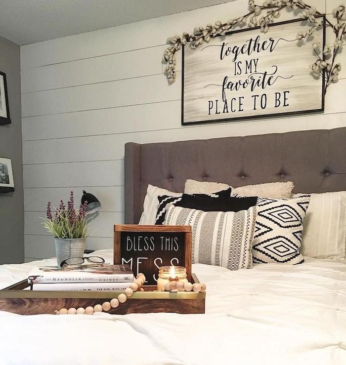 tête de lit grise, coussind décoratifs, noir, gris et blanc, linge de lit blanc, table de service bois avec decoration bougie, herbes, livres, vieille plaque publicitaire