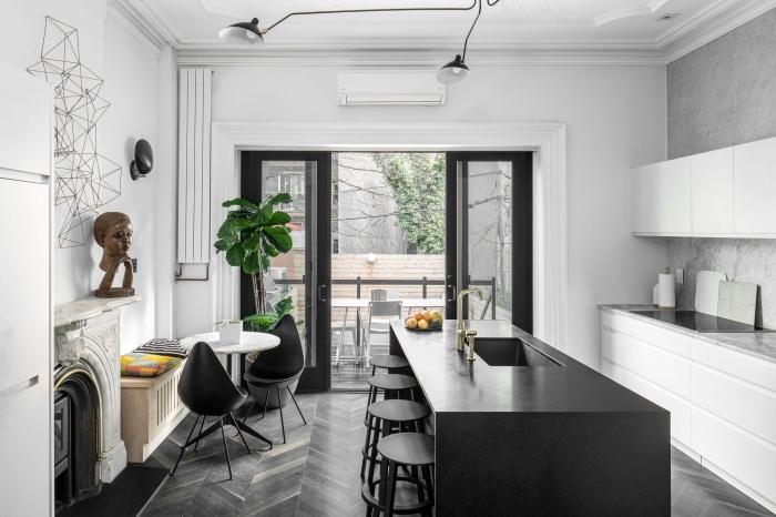 une petite cuisine blanche aménagée en longueur qui partage l'espace avec le salon design, séparée par l'espace séjour par un ilot de cuisine noir mat
