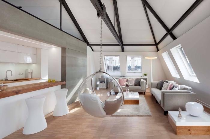 déco chaleureuse et cocooning dans un studio avec cuisine blanc et bois équipée d'ilot central, modèle de plafond mansarde en blanc et noir avec poutres