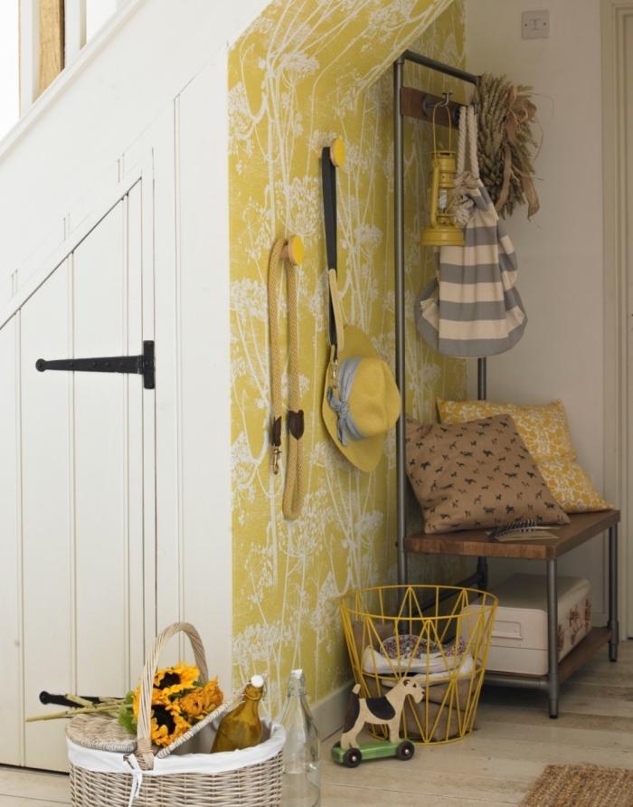 du papier peint à motifs champêtres jaune et blanc qui délimite joliment l'entrée et valorise l'espace sous escalier