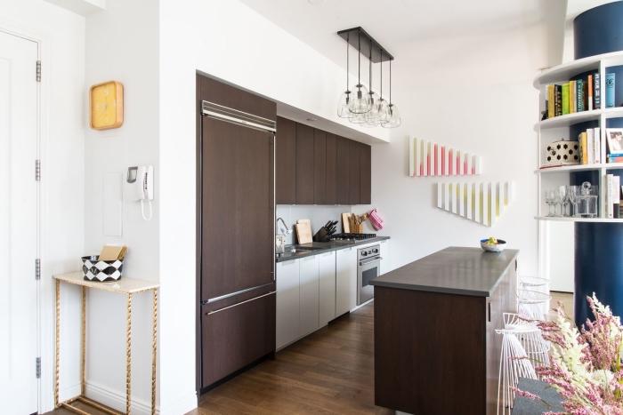 cuisine gain de place en couleur wengé équipée d'un ilot central table qui offre un espace de travail supplémentaire et qui joue le rôle de séparation entre cuisine et espace séjour