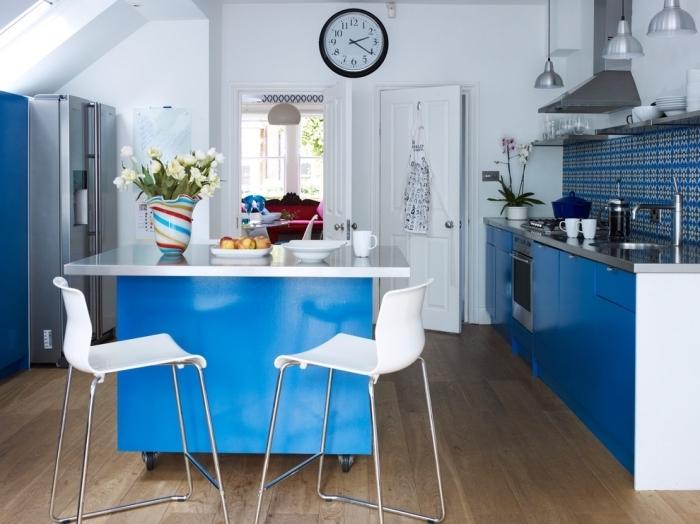 aménagement fonctionnel d'une petite cuisine avec ilot central à roulettes aux mêmes couleurs blanc et bleu que les armoires et la crédence
