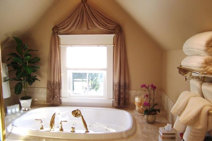 déco cozy dans une salle de bain sous combles aux murs beige avec petite fenêtre, exemple petite baignoire blanche avec robinet doré