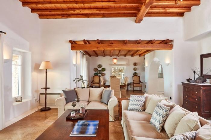 poutre decorative pour décorer le plafond dans un salon de style campagne ou rustique, meubles de bois foncé dans une pièce blanche