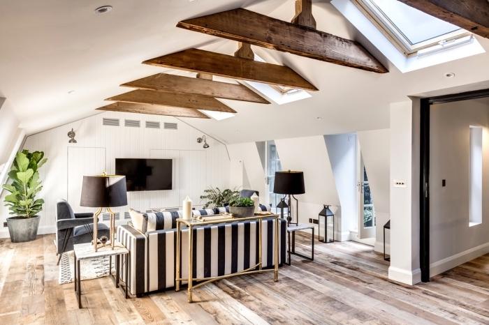 combiner les styles rustique et moderne dans un appartement mansardé au plafond blanc avec fausse poutre foncée ou en bois massif