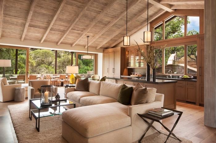 jolie déco accueillante dans un salon et cuisine ouverte avec meubles de bois et finitions en noir, modèle de plafond sous pente avec fausse poutre