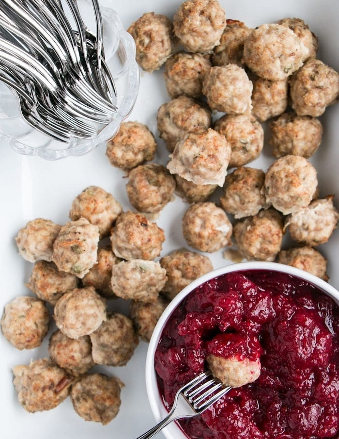 idée de boulettes à la viande hachée et herbes servies avec une confiture de canneberges, amuse bouche noel