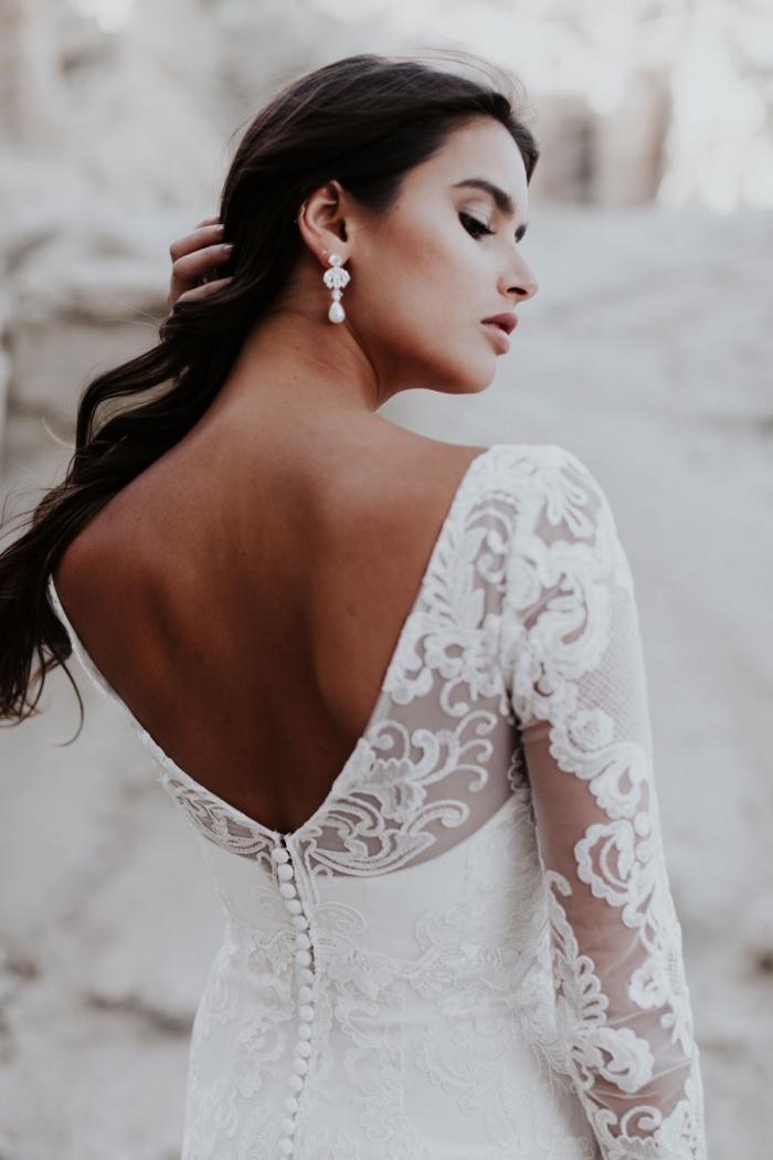 jolie robe de mariée à manche longue et à décolleté de dos plongeant en dentelle qui se termine par une rangée de petits boutons