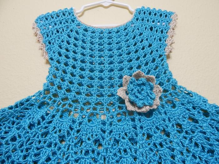 deco baby shower fille, robe tricotée au crochet en couleur bleue, avec une rose tricotée en beige et bleu sur le cote, cadeau future maman