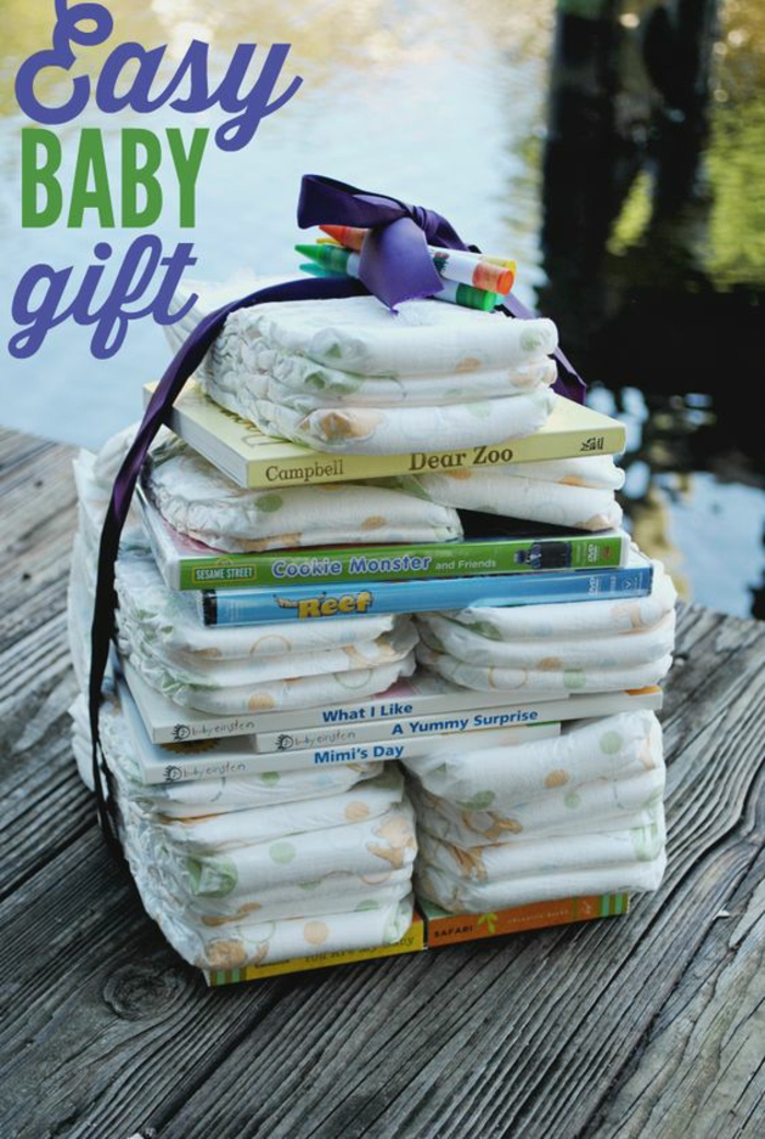 deco baby shower garcon, couches et livres bébé, organisées en pyramide, un cadeau facile a faire pour bébé, grand ruban en tissu bleu