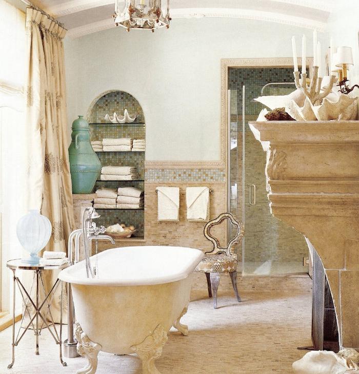 baignoire beige et blanc sur pieds, sol beige, cheminée décorative, niche murale rangement, chaise design vintage campagne