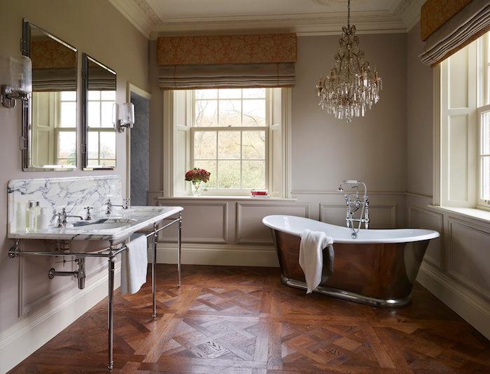 baignoire émaillée grise, parquet bois foncé, lavabo console vintage, grands miroirs, lustre vintage style baroque, murs couleur taupe, deco campagne chic