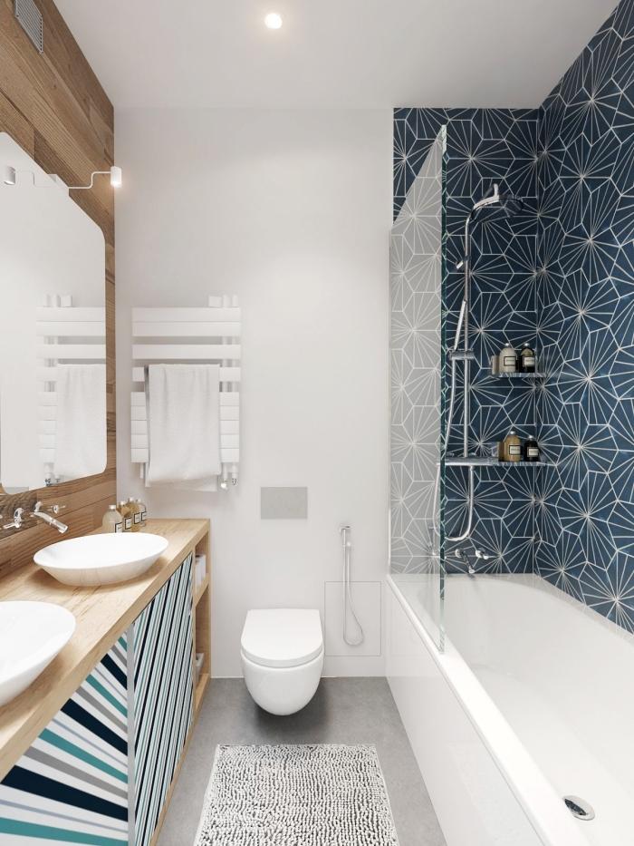 un pan de mur en carrelage carreaux de ciment à motifs graphiques modernes qui permet de délimiter la baignoire dans cette petite salle de bains