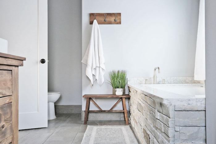 baignoire en pierre encastrée, sol en dalles carreaux de ciment, banc en bois, murs blancs, meuble lavabo bois brut