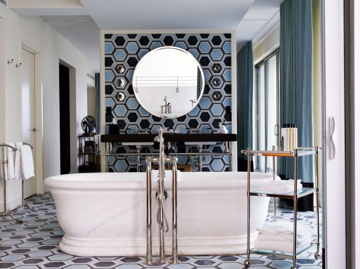 une baignoire îlot tendance au coeur de cette salle de bains de forte personnalité recouverte de carreaux de ciment à motifs hexagonaux noir et bleu