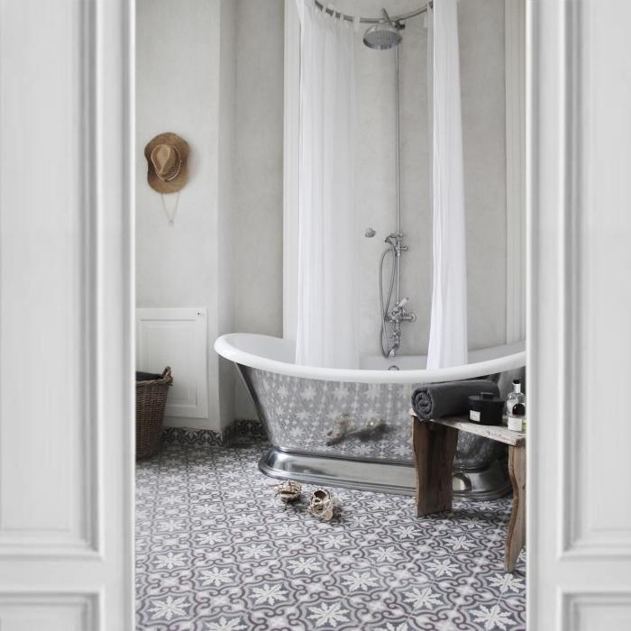 le revêtement de sol en carrelage carreaux de ciment à motifs arabesques délicats et l'aspect chromé de la baignoire créent une ambiance chic dans cette salle de bains monochrome