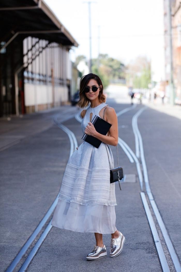 modèle de robe longue avec tulle et décolletée semi-ouverte de couleur bleu pastel combinée avec paire de derbyes métalliques argentés