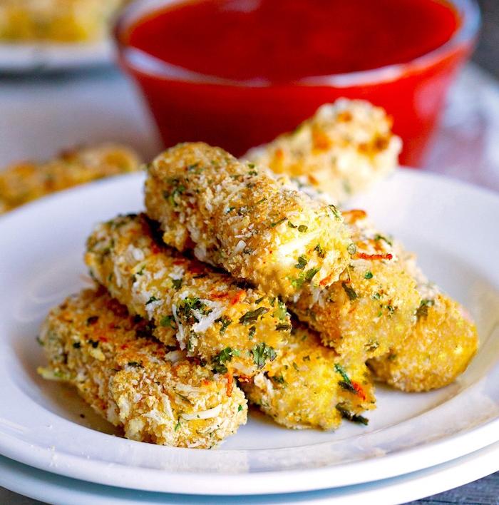 batons de mozzarella aux herbes fraiches, de la chapelure et fromage parmesan dans une assiette blanche