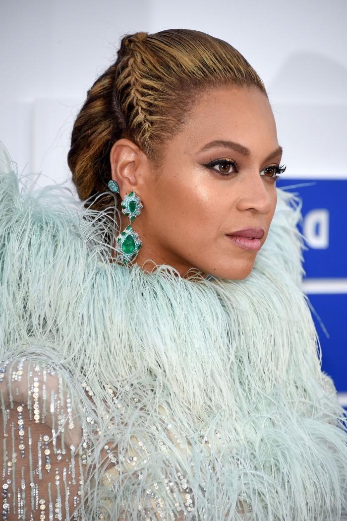 coiffure moderne et originale de Beyonce aux cheveux longs attachés en chignon avec une couronne de petite tresse plaquée, tresse sur le côté