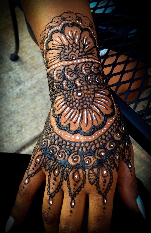 illustration au henné blanc et noir sur la main et le poignet femme