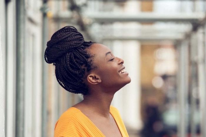 idée comment styliser les cheveux frisés femme, modèle de coiffure aux cheveux tressés et attachés en chignon haut décontracté